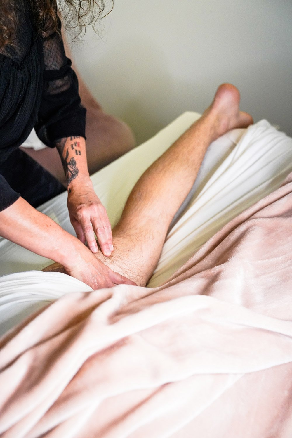 hands massaging man's leg at Blush Beauty Lounge
